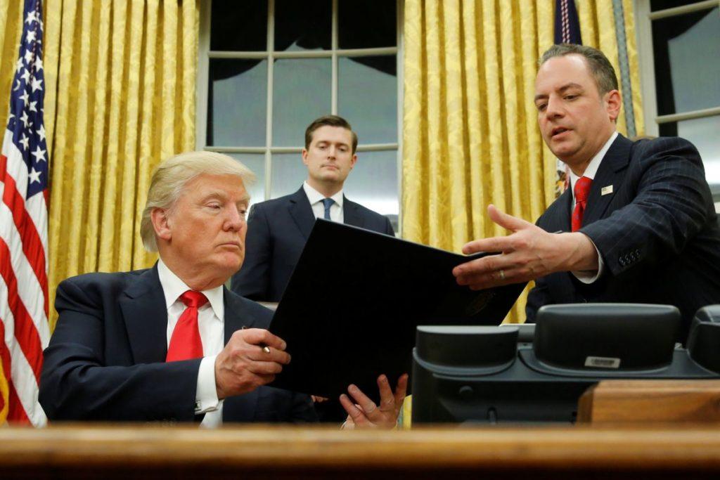 Дональд Трамп подписывает свой первый указ в качестве президента. Фото unian.net