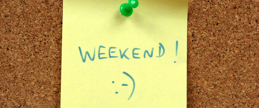 Yellow small sticky note on an office cork bulletin board. Weekend happiness.