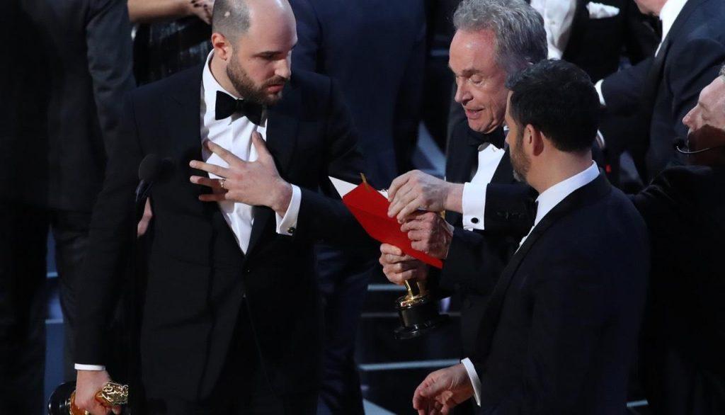 Продюсер «Ла-Ла Ленда» Фред Бергер (слева), актер Уоррен Битти (в центре) и ведущий «Оскара» Джимми Киммел во время объявления обладателя награды за лучший фильм года, 26 февраля 2017 года. Фото meduza.io