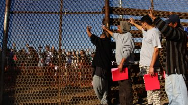 """A group of recently deported immigrants stand near the double steel fence that separates San Diego and Tijuana at the border in Tijuana December 10, 2011. Immigrants rights organizations from the U.S and Mexico on Saturday organized an annual pre-Christmas celebration called """"Posadas sin Fronteras"""" or """"Christmas without borders"""", which more than 200 people from both sides attended on the Tijuana and San Diego border. REUTERS/Jorge Duenes (MEXICO - Tags: SOCIETY IMMIGRATION)"""