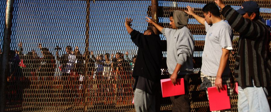 "A group of recently deported immigrants stand near the double steel fence that separates San Diego and Tijuana at the border in Tijuana December 10, 2011. Immigrants rights organizations from the U.S and Mexico on Saturday organized an annual pre-Christmas celebration called ""Posadas sin Fronteras"" or ""Christmas without borders"", which more than 200 people from both sides attended on the Tijuana and San Diego border. REUTERS/Jorge Duenes (MEXICO - Tags: SOCIETY IMMIGRATION)"