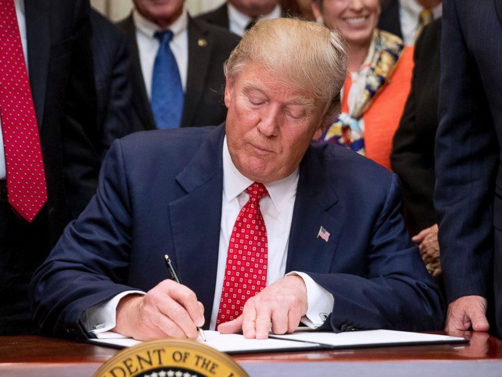 Трамп подписывает один из исполнительных указов. Фото: abcnews.go.com